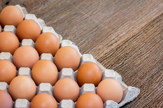 Nahaufnahme hühnereier in einem papierbehälter auf hölzernem hintergrund. braune eier, zum kochen