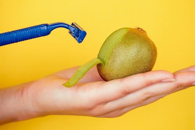 Nahaufnahme in der handfläche, die eine saftige fruchtkiwi und ein rasiermesser auf gelbem hintergrund hält. depilation und epilationsidee zur pflege des körpers.