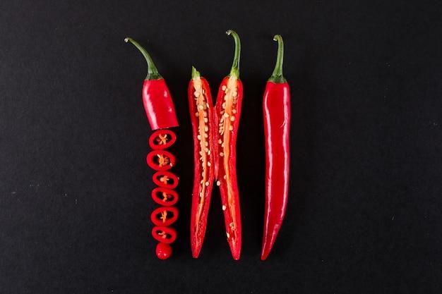 Nahaufnahme in scheiben geschnitten rote chili-pfeffer auf schwarzer oberfläche isoliert