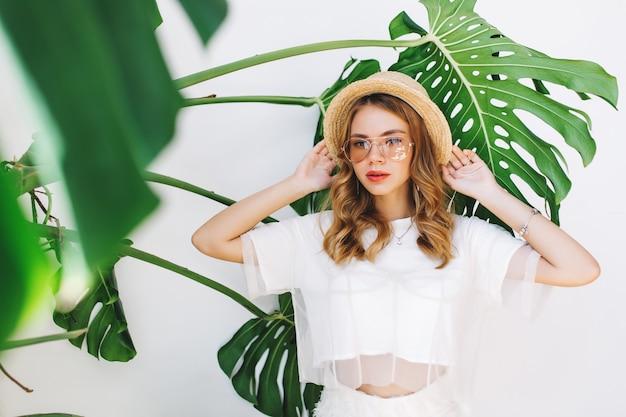 Nahaufnahme innenporträt des stilvollen mädchens trägt sommerhut und brille, die nahe großer grüner pflanze stehen