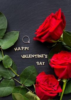 Nahaufnahme inschrift glücklicher valentinstag mit roten rosen und ehering