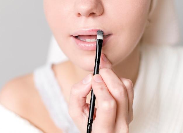 Nahaufnahme junge frau, die lippenstift anwendet