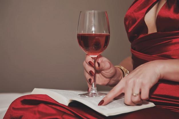 Nahaufnahme junge frau im kleid mit tiefem ausschnitt mit glas wein lesebuch zum valentinstag im hotelzimmer