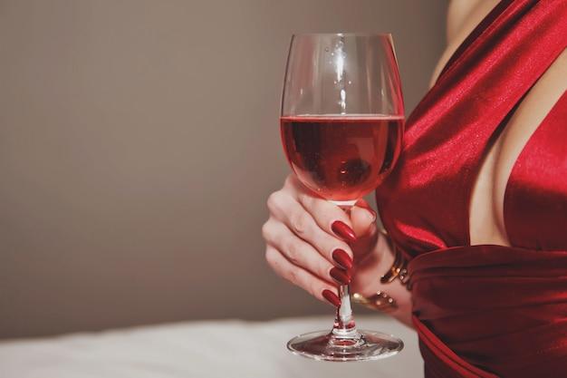 Nahaufnahme junge frau im kleid mit tiefem ausschnitt mit glas wein zum valentinstag im hotelzimmer
