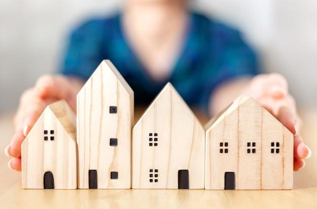 Nahaufnahme junge geschäftsfrau wählt haus, hausmodell aus vielen möglichkeiten für den bau aus, damit menschen kaufen, kaufen, verkaufen oder in die finanzierung zur miete eines modernen konzeptprojekts von immobilien investieren können