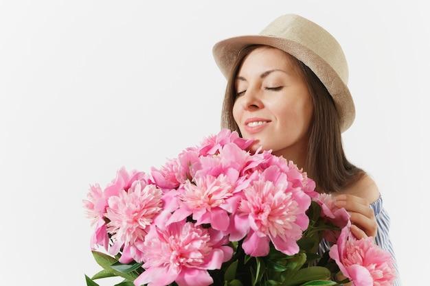 Nahaufnahme junge zarte frau in kleid hut hält, bouquet von rosa pfingstrosen blumen auf weißem hintergrund schnüffeln. st. valentinstag internationaler frauentag-feiertagskonzept. werbefläche