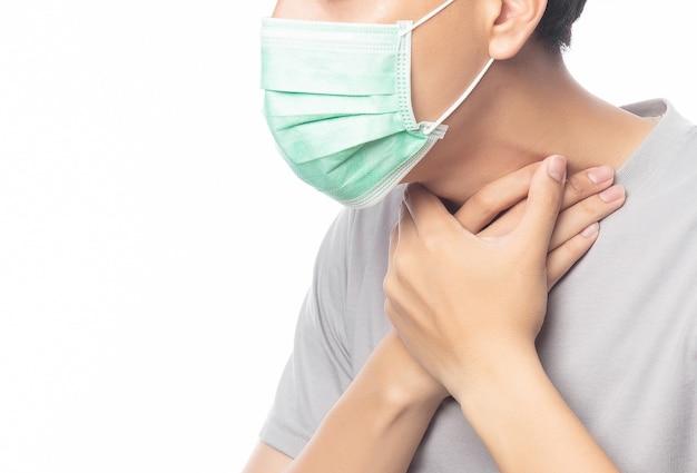 Nahaufnahme junger mann in der hygienemaske, die halsschmerzen leidet