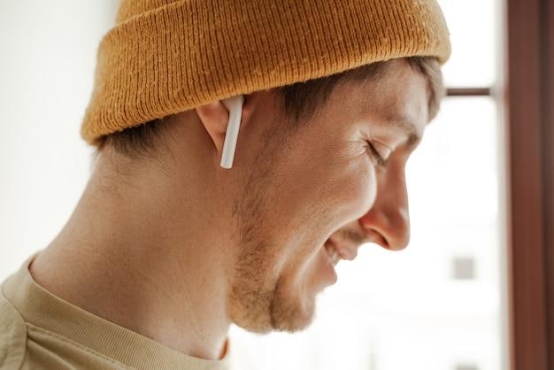 Nahaufnahme junger reisender, der im sommerurlaub musik in airpods im hotelzimmer hört.