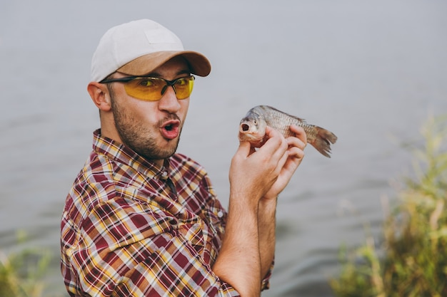 Nahaufnahme junger unrasierter mann in kariertem hemd, mütze und sonnenbrille hat einen fisch gefangen, zeigt ihn und freut sich am ufer des sees auf dem hintergrund des wassers. lifestyle, erholung, freizeitkonzept für fischer