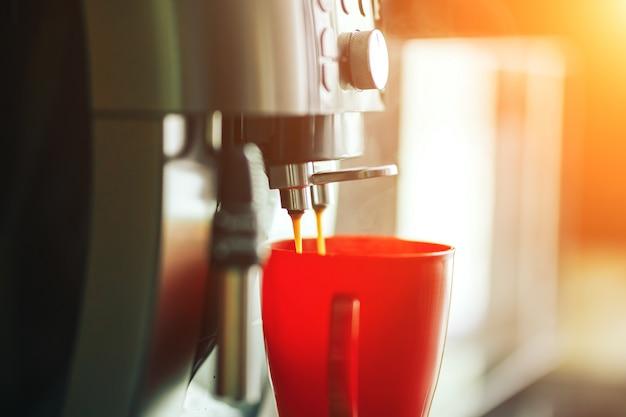 Nahaufnahme kaffeemaschine, die morgens frischen kaffee macht, kaffeemaschine und rote tasse