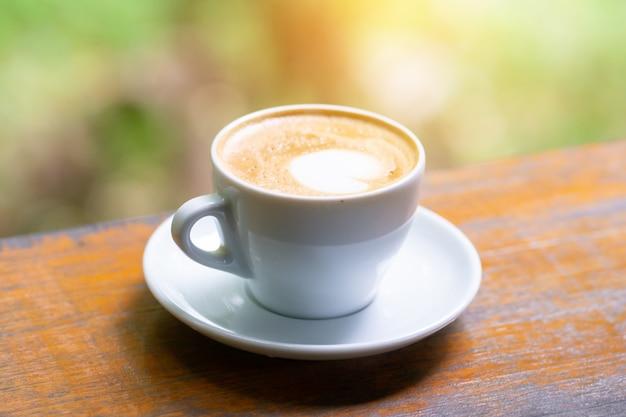 Nahaufnahme kaffeetasse auf holztisch, grüner baum bokeh hintergrund