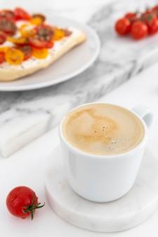 Nahaufnahme kaffeetasse und sandwiches mit frischkäse und tomaten