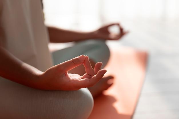 Nahaufnahme kind, das auf matte meditiert