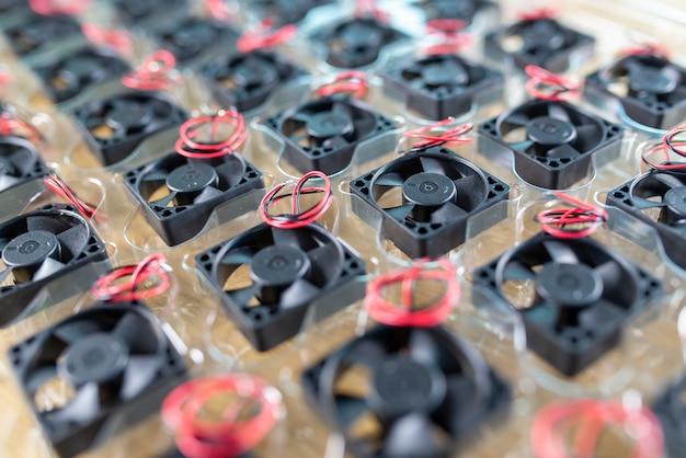 Nahaufnahme kleine kunststoff-computerkühler mit drähten liegen in transparenter kunststoffverpackung auf einem holztisch bei der herstellung von computern. konzept der computer- und gerätefabrik