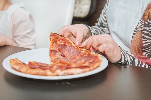 Nahaufnahme. kleine teilnehmer der meisterklasse essen pizza. gemeinsam pizza kochen