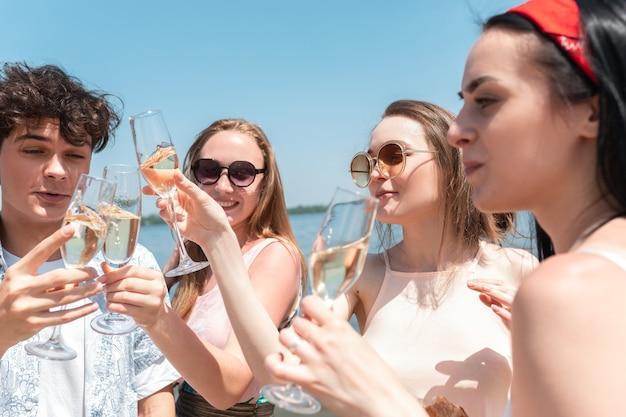 Nahaufnahme klirren, prost. saisonales fest im strandresort. gruppe von freunden, die am sonnigen sommertag feiern, sich ausruhen, spaß haben. sehen sie glücklich und fröhlich aus. festliche zeit, wellness, urlaub, party.