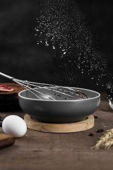 Nahaufnahme kochpfanne mit schneebesen auf dem tisch