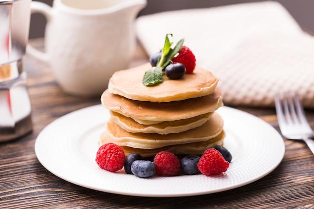 Nahaufnahme köstliche pfannkuchen mit frischen blaubeeren und himbeeren