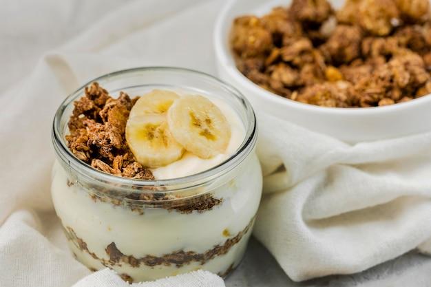 Nahaufnahme köstlicher joghurt mit müsli und banane