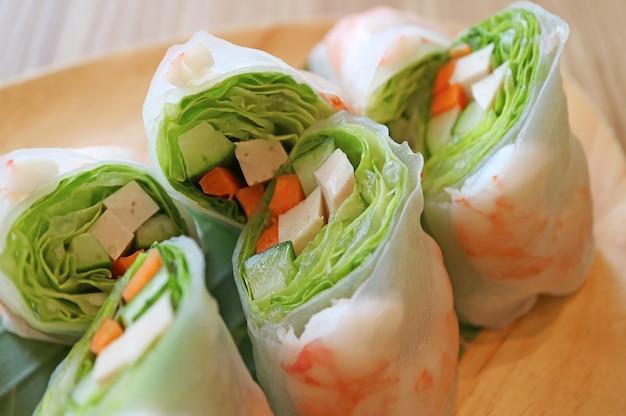 Nahaufnahme köstliches frisches gemüse mit garnelenfrühlingsrollen auf einer holzplatte
