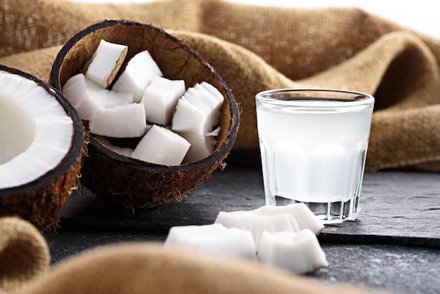 Nahaufnahme-kokosnusshälften und kokosnusswasser im glasschuss auf leinwandgewebe auf grauem hintergrund
