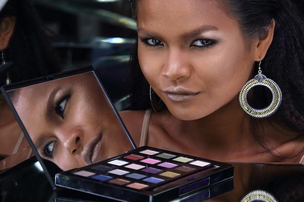 Nahaufnahme kopf geschossen von 20er jahre asiatische frau mit mode make-up über spiegel reflektieren ihr gesicht. gebräunte hautmädchen betrachten kosmetikpalette für make-up mit dunklem hintergrund des reflexionswinkels
