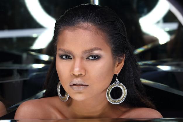 Nahaufnahme kopf geschossen von 20er jahre asiatische frau mit mode make-up über spiegel reflektieren ihr gesicht. gebräuntes hautmädchen, das sich stark fühlt, lächelt, glücklich mit dunklem hintergrund des reflexionswinkels