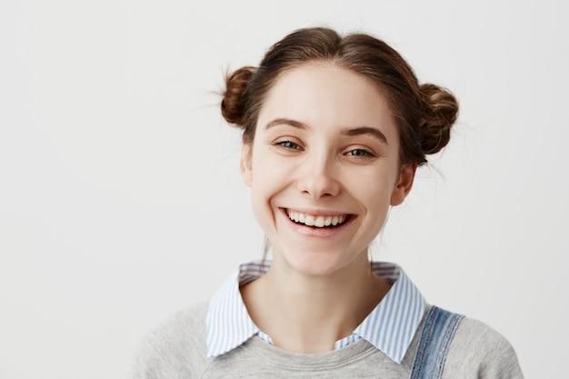 Nahaufnahme kopfschuss der absolut glücklichen frau, die mit breitem lächeln kichert. freudige gefühle einer unbeschwerten studentin, die nach bestandener prüfung gute laune hat.