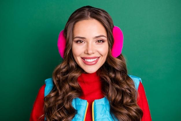 Nahaufnahme-kopfschuss-foto einer süßen, reizenden jungen dame, die zahnig lächelnd wartet, freund, verschneiter tag, datum tragen rosa ohrwärmer blaue weste roter pullover isoliert grüner farbhintergrund