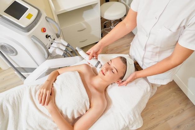 Nahaufnahme kosmetikerin macht ultraschall hardware reinigung des gesichts ihrer patientin eine schöne junge frau. konzept hautreinigung und wiederherstellung der elastizität