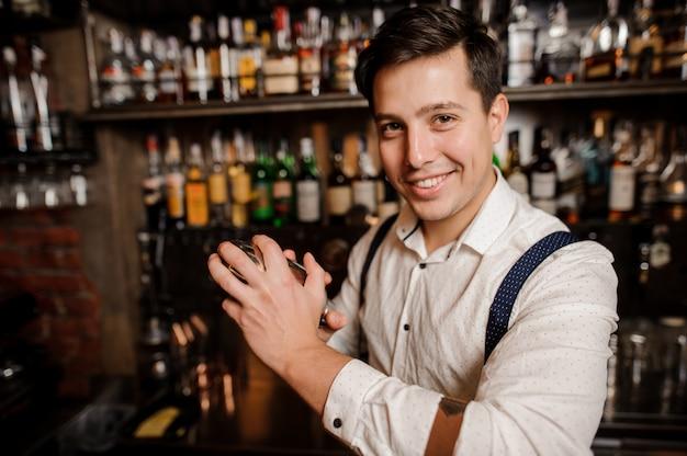 Nahaufnahme lächelnd barkeeper einen cocktail machen