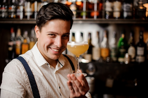 Nahaufnahme lächelnd barkeeper hält einen orangefarbenen cocktail