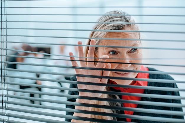 Nahaufnahme. lächelnde geschäftsfrau, die durch büro-jalousien schaut.