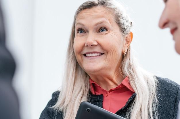 Nahaufnahme. lächelnde geschäftsfrau im gespräch mit ihren kollegen. büro wochentags