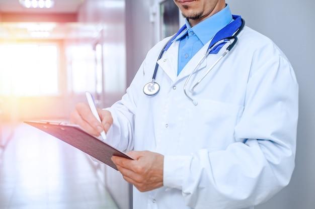 Nahaufnahme lächelnder männlicher arzt. junger arzt mit stethoskop in der krankenhaushalle