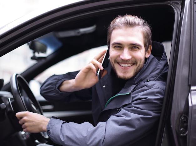 Nahaufnahme. lächelnder mann, der auf handy im auto spricht.