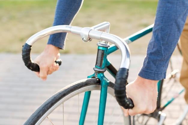 Nahaufnahme lässiger mann, der fahrrad draußen reitet