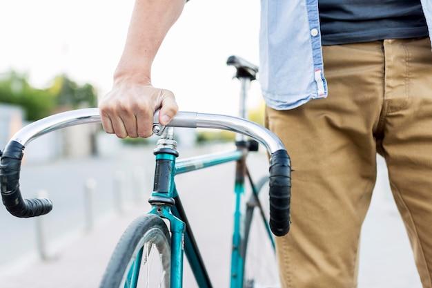 Nahaufnahme lässiger mann, der sein fahrrad hält