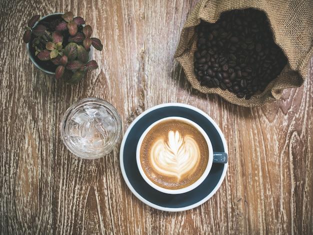 Nahaufnahme lattekunst der braunen kaffeetasse des kaffees auf holztischoberfläche