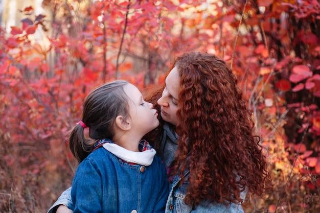 Nahaufnahme liebeskonzept süßes kleines mädchen küsst ihre mutter mit langen kurvigen haaren auf herbstlichem waldhintergrund