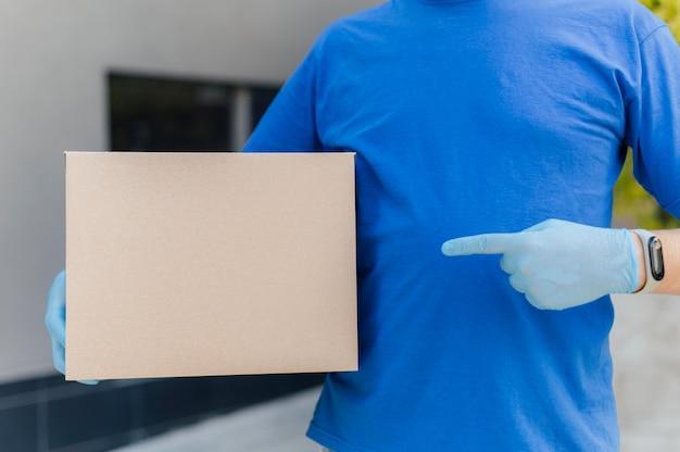 Nahaufnahme-lieferbote, der auf kasten zeigt