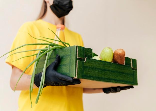 Nahaufnahme-lieferfrau, die nahrungsmittelkiste hält