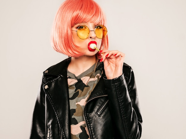 Nahaufnahme lippen des jungen schönen hipster bösen mädchens in der trendigen schwarzen lederjacke und ohrring in der nase. sexy sorglos lächelnde frau posiert im studio in der rosa perücke. positives modell leckt runde süßigkeiten