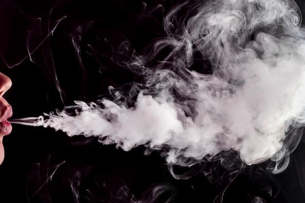 Nahaufnahme lippen, die dampfrauch (e-zigarette) mit platz für text freisetzen