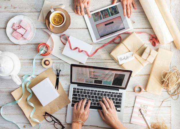Nahaufnahme luftaufnahme der hände unter verwendung von laptop und tablette mit verpackten geschenken