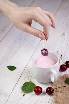 Nahaufnahme mädchenhände halten frische kirsche über glas mit joghurt, heller holztisch. leckeres frühstück und ein guter start in den tag