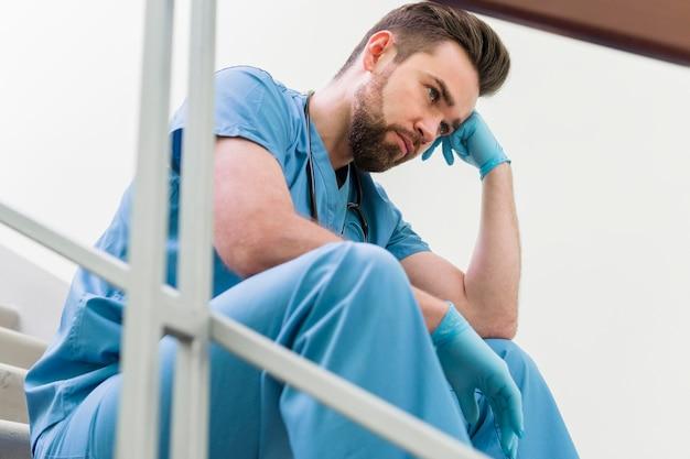Nahaufnahme männliche krankenschwester, die eine pause bei der arbeit macht