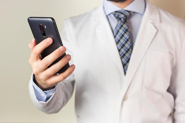 Nahaufnahme männlichen doktors, der intelligentes telefon gegen farbigen hintergrund verwendet