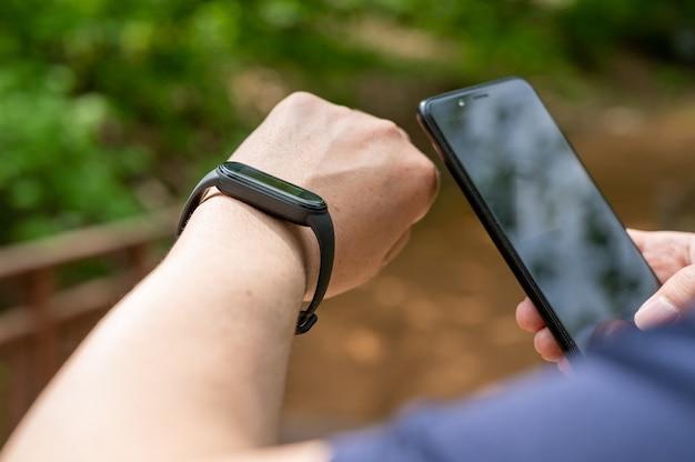 Nahaufnahme männlicher hände, die smartwatch und smartphone auf der promenade halten holding