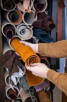 Nahaufnahme männlicher handwerker, der materialbündel für die arbeit in der lederwerkstatt nimmt, die lederwaren herstellt?